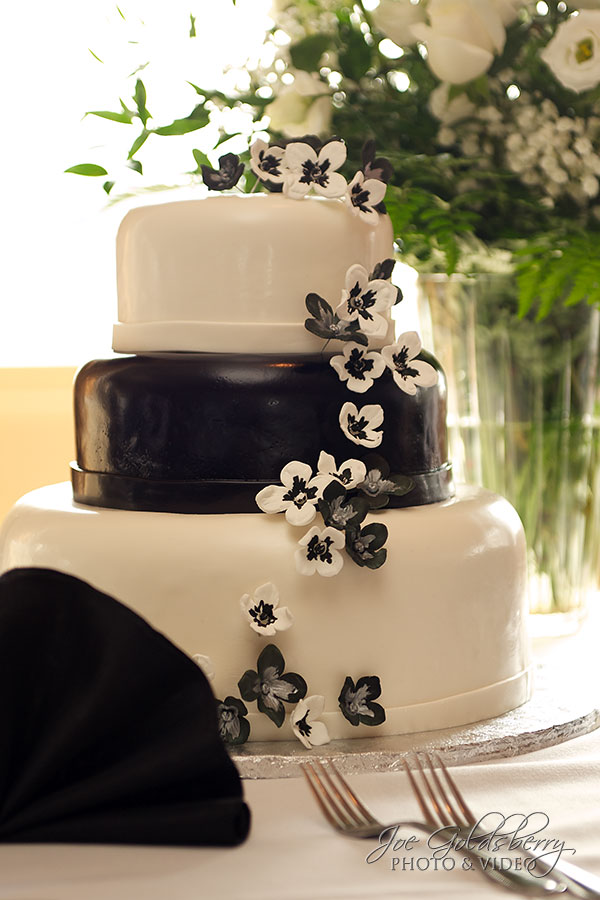 The wedding cake was a three tiered black and white cake with cascading flowers, prepared by White's Fine Cakes and Pastires.